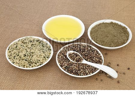 Hemp health food with hulled and dried seed, oil and powder in porcelain bowls with spoon on hessian background.