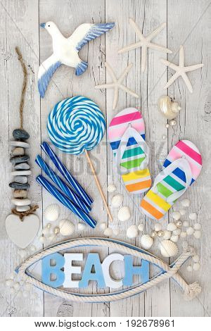 Abstract beach art collage with flip flops, candy rock, seashells, pearls and decorative seaside items on distressed white wood forming a background. Summer holiday concept.