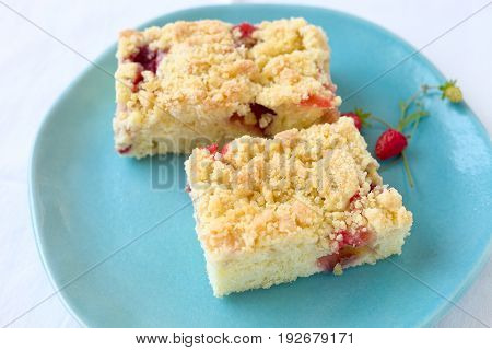 Slice of crumble strawberry cake on a blue plate.