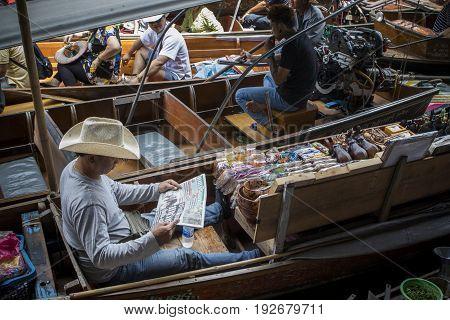 RATCHABURI THAILAND - JUNE 26,2017 : thai boat vender reading thai news paper and tourist boat passing in dumnoen saduak floating market ratchaburi thailand