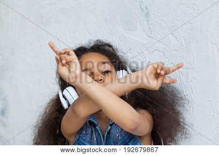 cute African girl listening to music in big white headphones With crossed arms covers her face