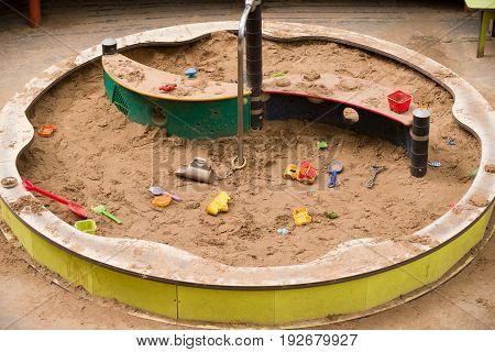 Top view on sandbox with children colorful plastic toys. Outdoor.