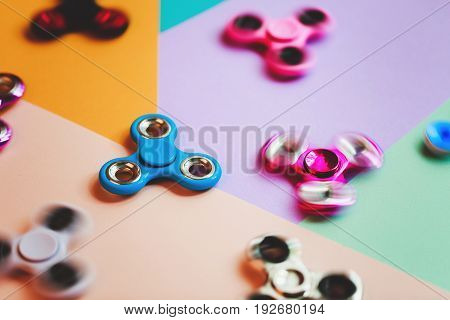 Set of fidget spinners on multicolored background.