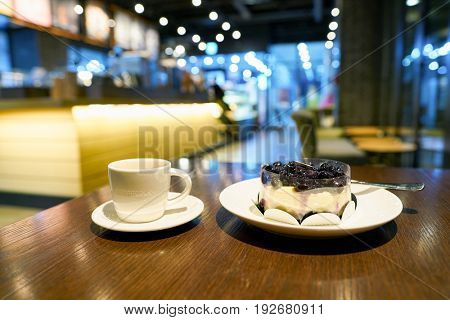 SEOUL, SOUTH KOREA - CIRCA MAY, 2017: a cup of coffee and blueberry cheese cake on a table in Starbucks. Starbucks Corporation is an American coffee company and coffeehouse chain.