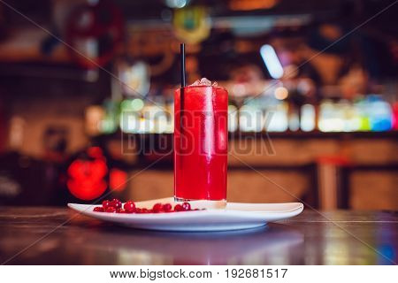Cranberry juice in a glass on a white plate decorated with cranberry.