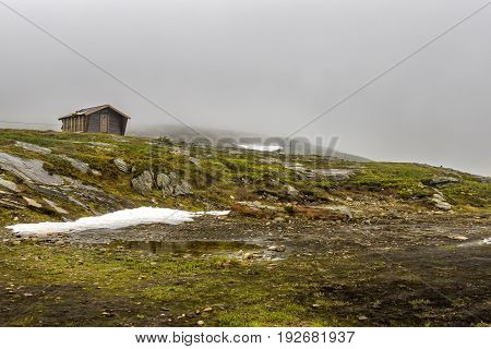 Lonely Wooden House Stands On The Hill Among North Norway Nature.