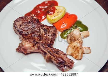 Steak with vegetables grilled served on a white plate.