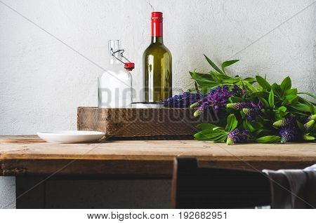 Bouquet of lupines and ware on an old wooden table against the background of a white concrete wall