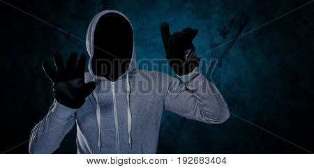 Robber with hood and gloves against dark background