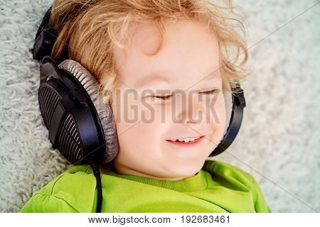 Little 3 year old boy listening to music in headphones.