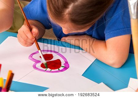 Small student girl painting heart in art school class. Child drawing by paints on table. Mother day holiday. Kid in a children's club. Craft drawing education develops creative abilities of children.