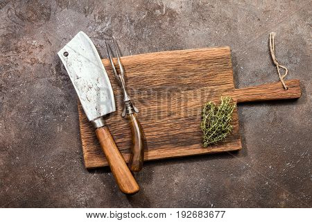 Vintage Meat cleaver, fork and cutting board on dark brown stone background
