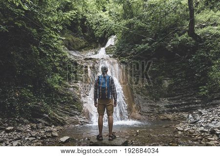Traveler Reached Destination And Enjoys View Of Waterfall Rear View Contemplation Adventure Concept
