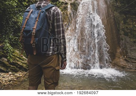 Unrecognizable Young Man Has Reached Destination And Enjoying View Of Waterfall. Journey Hiking Adventure Concept