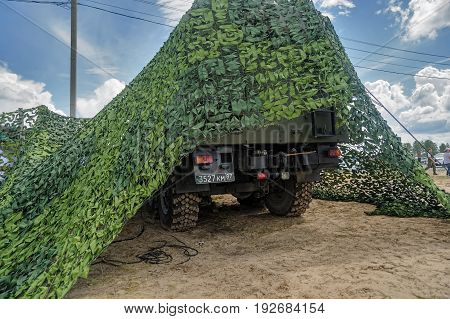 Military Vehicle Stands Under Camouflage Nets