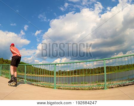 Rear View To Inline Skater In Red T-shirt And Black Pants Skating On The Bridge . Outdoor Inline Ska