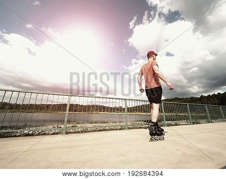 Middle Age Man In Red T-shirt  With Inline Skates Ride In Summer Park, Popular Outdoor Skating.