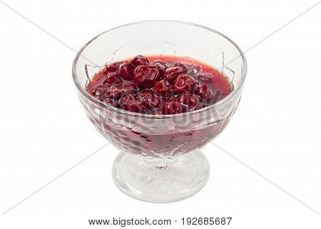 Cherry jam with whole fruits in the glass dessert stem bowl on a light background