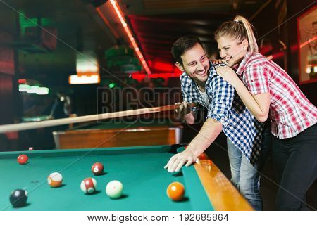 Young couple playing pool in bar while having night out in town