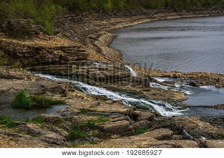 Rocky spillway waterfall between two large lakes