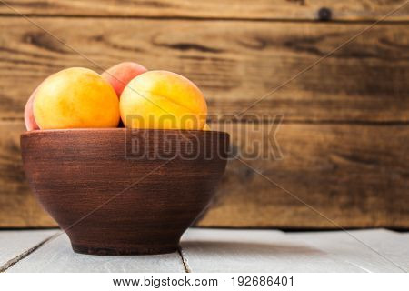 Bowl Of Ripe Apricot On A Wooden Background