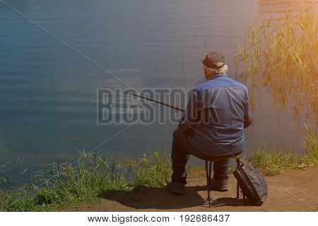Fisherman With Fishing Rod Catching Fish, Sitting Riverside. Sunlight