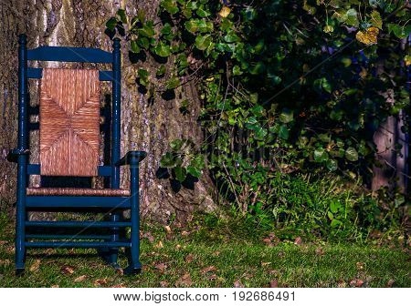 blue wicker rocking chair outdoors near a large tree