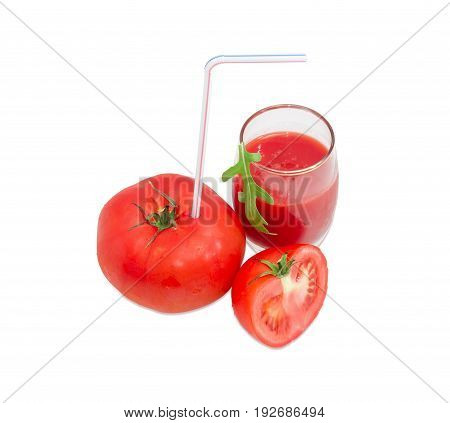Big fresh whole tomato with bendable drinking straw inserted into it half of the tomato and glass with tomato juice and arugula leaf on a light background