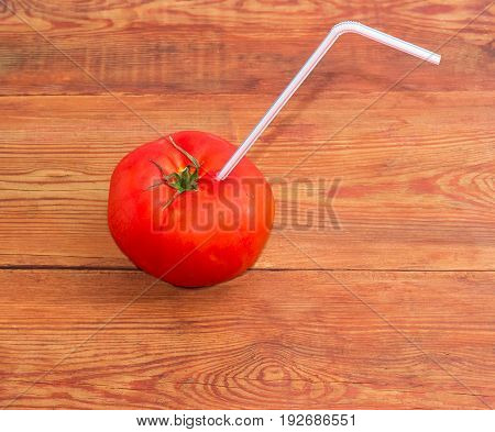Big fresh ripe tomato with bendable drinking straw inserted into it on a surface of the old wooden planks