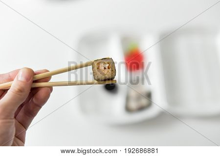 Hand Keep Roll With Chopsticks, Rolls, Sushi. Chopsticks, Ginger, Soy Sauce In Container Delivery.