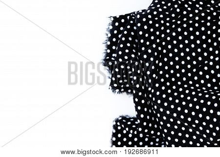 Piece of black fabric with a pattern of white peas isolated on a white background.