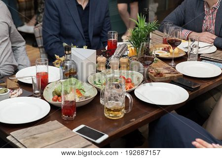 Friendly Dinner. Group Of People Having Dinner Together While Sitting At The Rustic Wooden Table