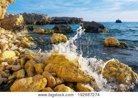 Splashing waves on rocks and stones. Sea coast in Crimea