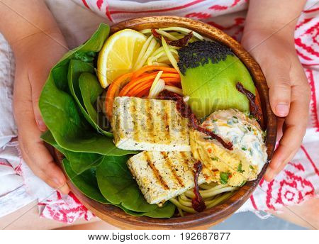 Buddha bowl with grilled tofu and vegetables in the child's hands. Child vegan concept.