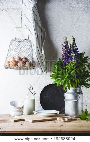 Concept Of Rural Kitchen. Lupines In A Can, Milk, Eggs And Ware On A Wooden Table Against The Backgr