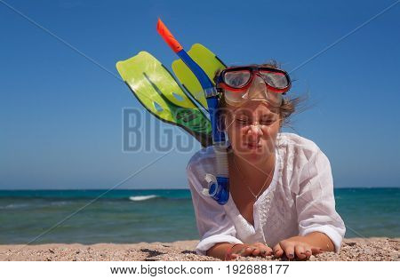 A young woman in a mask and fins for snorkeling, lies on the sand and laughs. The concept of a fun holiday on the beach.