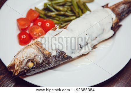 Grilled sea bass served on a plate with various sauces and and vegetables