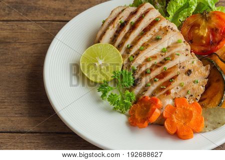 Sliced chicken breast barbecue on white plate served with grilled vegetable. Delicious chicken breast steak and salad for dinner. Homemade chicken breast barbecue on wood table for background. Chicken steak or pork chops background.