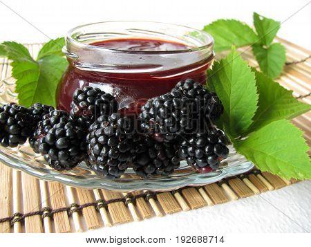 Homemade blackberry jelly in jar and fresh blackberries