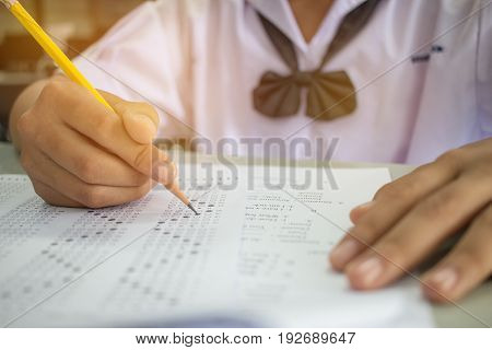 Asian student testing english exam or exercise on exams answer sheets with pencil in class room at school Thai education concept