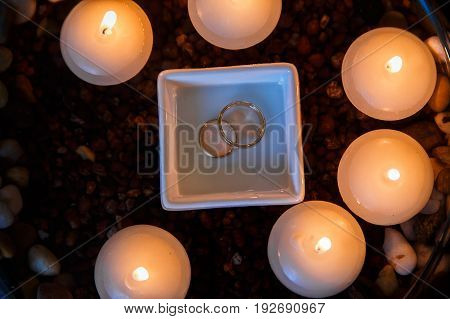 A beautiful composition of wedding diamond rings with glowing floating candles in the water.