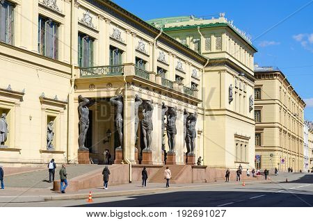 SAINT PETERSBURG RUSSIA - MAY 3 2017: Unknown people walk along Millionnaya Street near building of New Hermitage St. Petersburg Russia