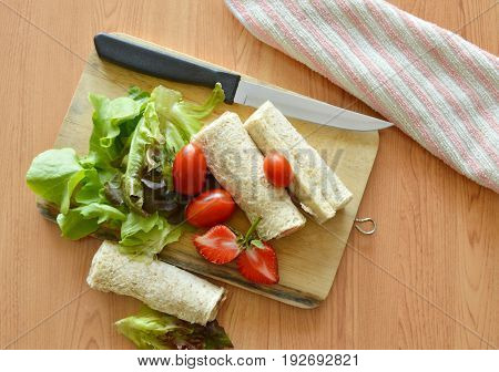 bread roll and salad on wooden cutting board