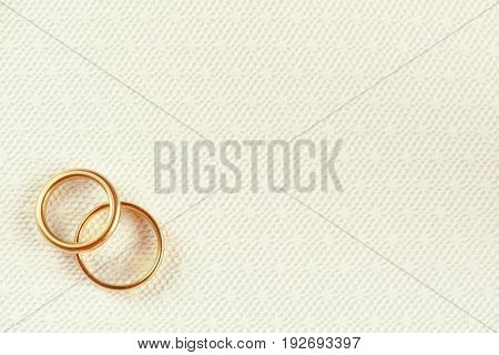 Two golden wedding rings over white wedding lace with floral pattern. Wedding card concept
