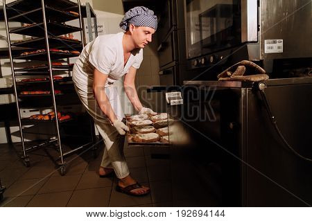 Baker taking a loaf of freshly baked bread from the oven in a modern bakery, the Baker taking fresh bread