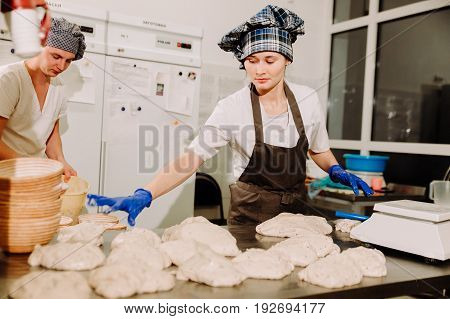 a Baker prepares dough for bread in the bakery, two of the Baker preparing dough for bread