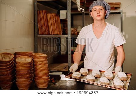 Baker with a tray with a test looking at the camera, a Baker makes manual incisions on the dough for the bread