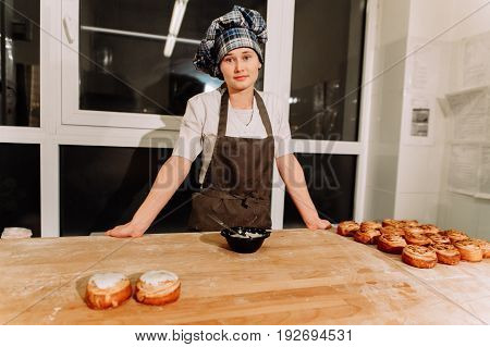 Woman bake pies. Confectioners make desserts. Making buns. Dough on the table. Knead the dough.