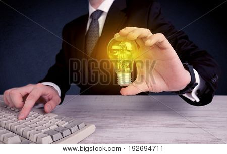 A business man in suit holding a glowing yellow light bulb in his hand while working in the office concept.