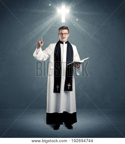 A young caucasian priest with deep faith blessing with the holy bible in his hand in front of blue wall background with illustrated glowing cross concept.